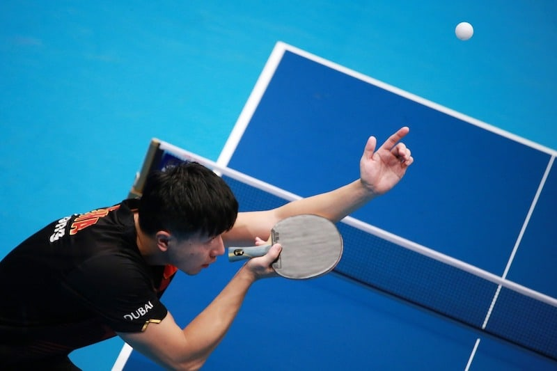 table tennis player tossing ball for serve